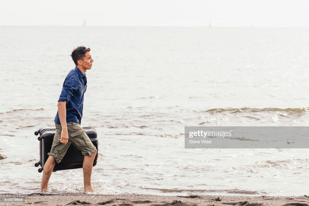 Man Carrying Suitcase And Walking On The Beach : ストックフォト