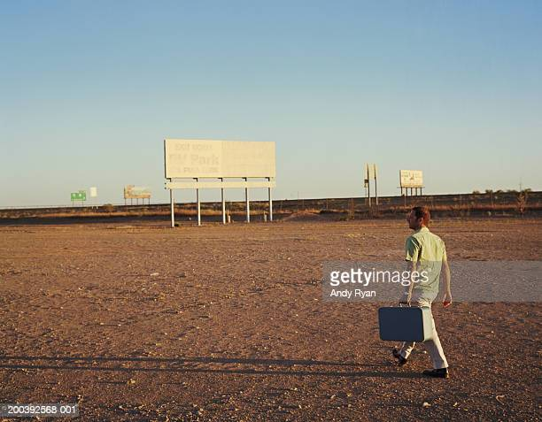 Man carrying suitcase walking across truck stop in desert landscape