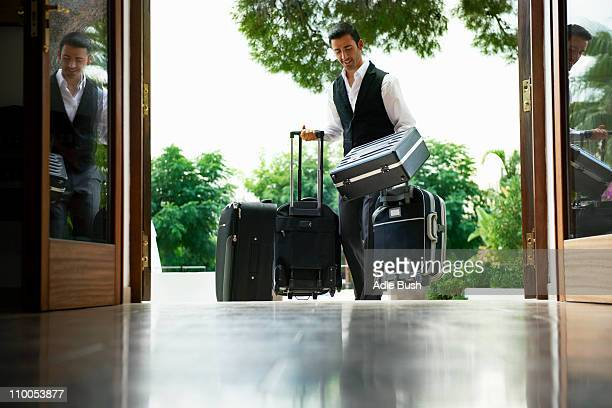Man carrying suitcases into hotel
