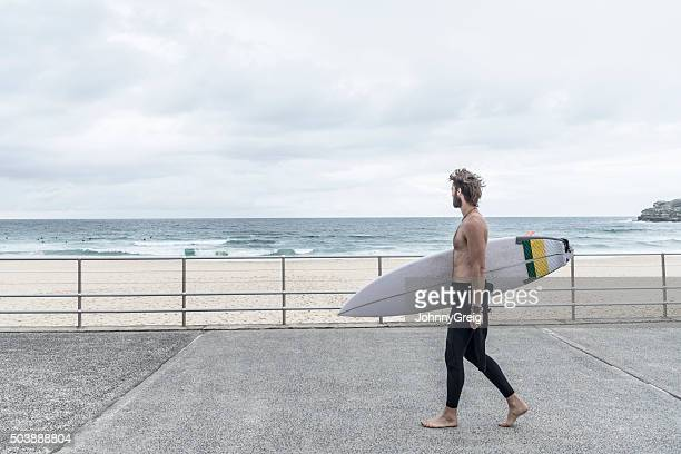 Man carrying surfboard along promenade, Bondi Beach