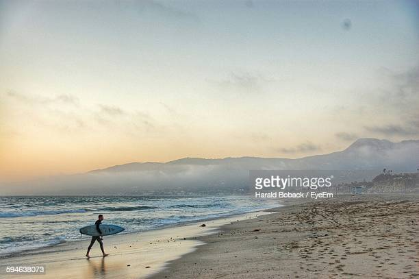 man carrying surfboard at beach against sky - santa barbara stock photos and pictures