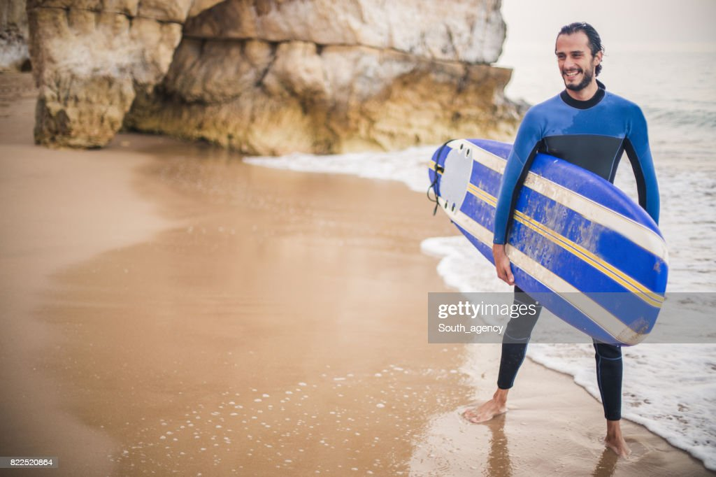 Man carrying surfboard at the beach : Stock Photo