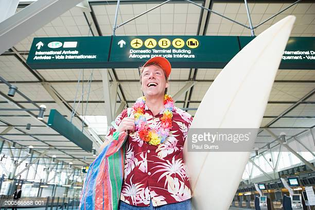 Man carrying surfboard in airport, smiling