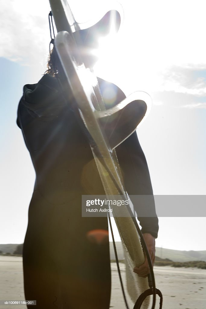 Man carrying surfboard on beach, low angle view : Stockfoto