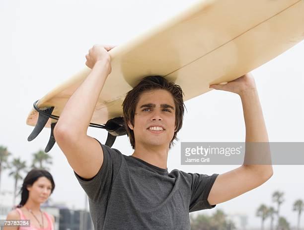 Man carrying surfboard on head