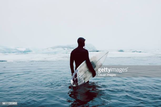 man carrying surfboard while standing in icy sea against clear sky during winter - surfer stock-fotos und bilder