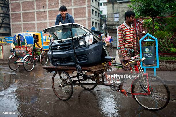 OLD DHAKA DHAKA BANGLADESH A man carrying the front of a car on a rickshaw in the street during a rainy day the first day of Ramadan in old Dhaka...