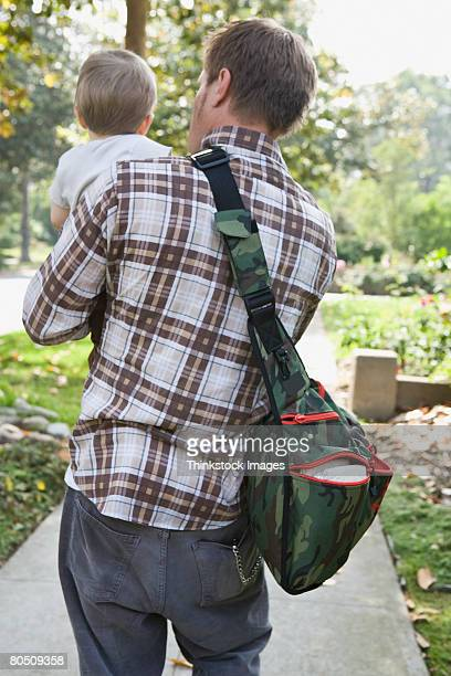 man carrying toddler - diaper bag stock pictures, royalty-free photos & images