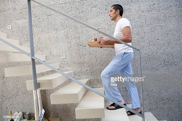Man carrying tray of food up stairs