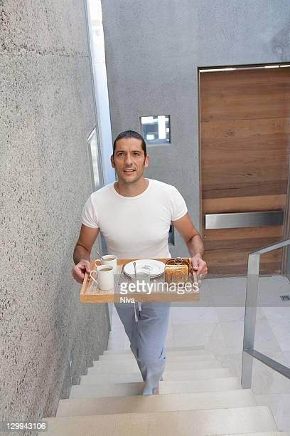 Mann mit Teller mit Essen auf Treppe
