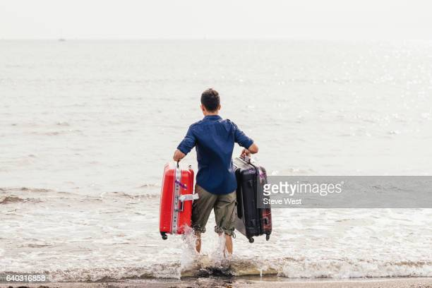 Man Carrying Two Suitcases Walking Into The Ocean