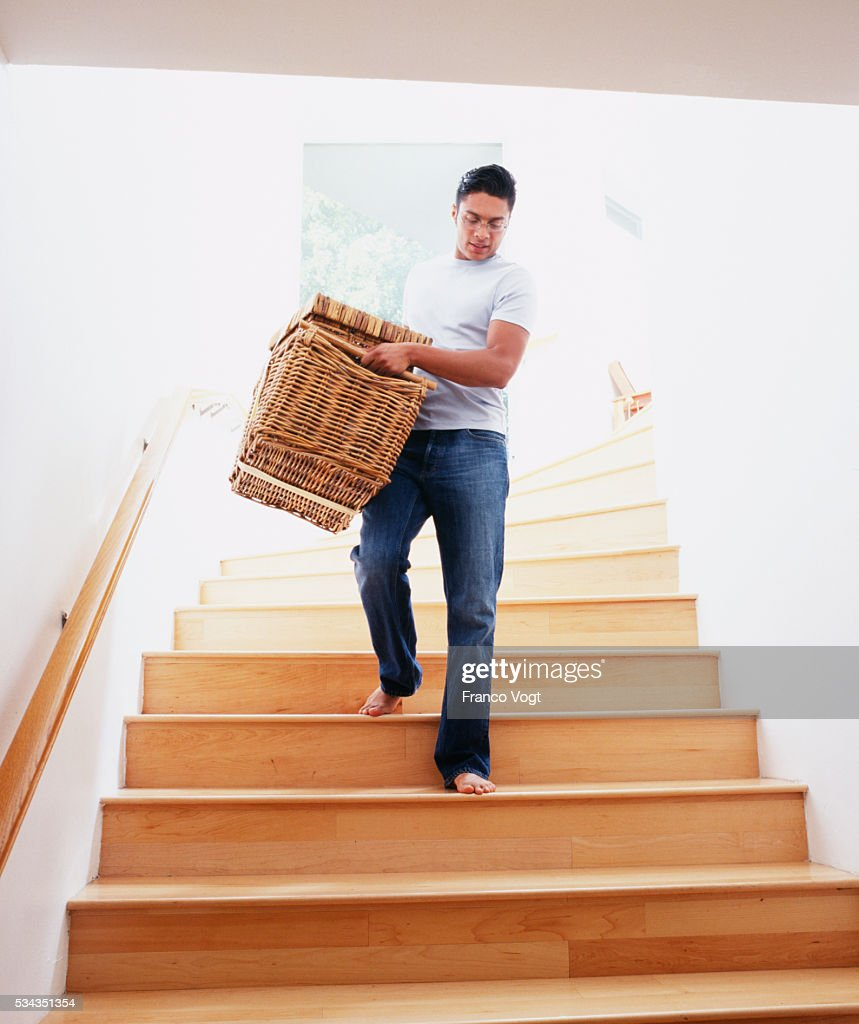 Man Carrying Wicker Basket Down Stairs : Stock Photo