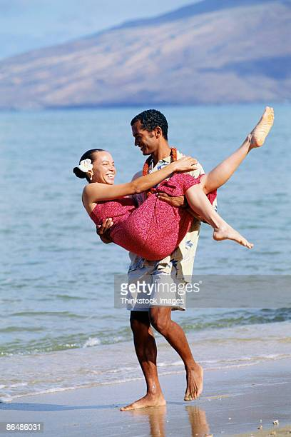 man carrying woman along beach, maui, hawaii - media_in_honolulu,_hawaii stock pictures, royalty-free photos & images