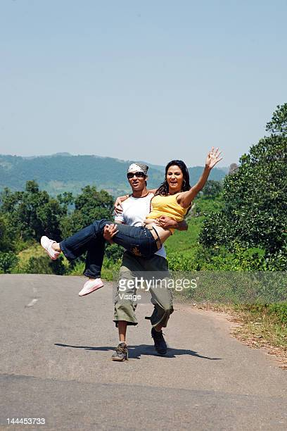 Man carrying woman and walking on the road