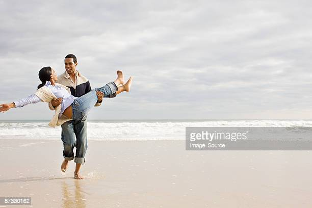 Man carrying woman by the sea
