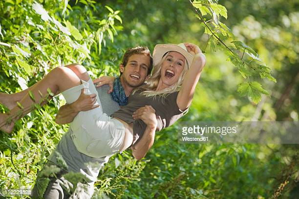 man carrying woman in forest, smiling - バミューダパンツ ストックフォトと画像