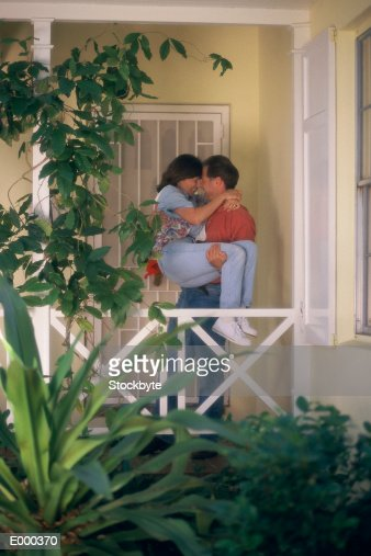 Man Carrying Woman In His Arms Standing At Front Door Of