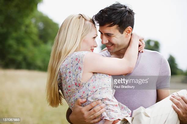 Man carrying woman in rural field