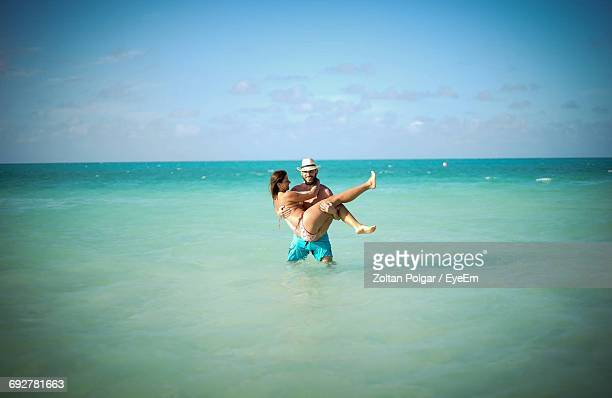 Man Carrying Woman In Sea Against Sky