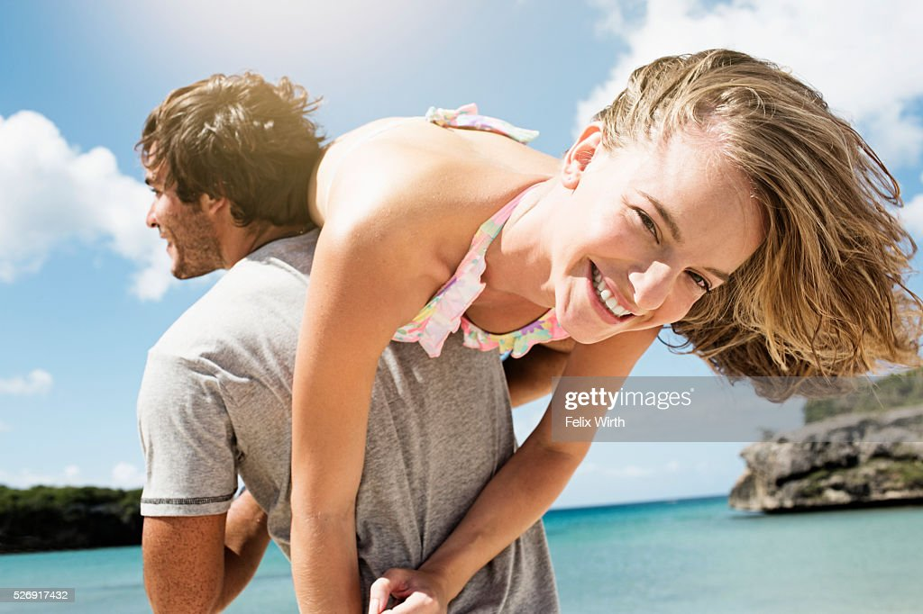 Man carrying woman on beach : Stock Photo