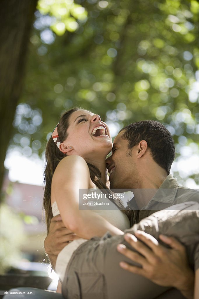 Man carrying woman on city street laughing : Foto stock