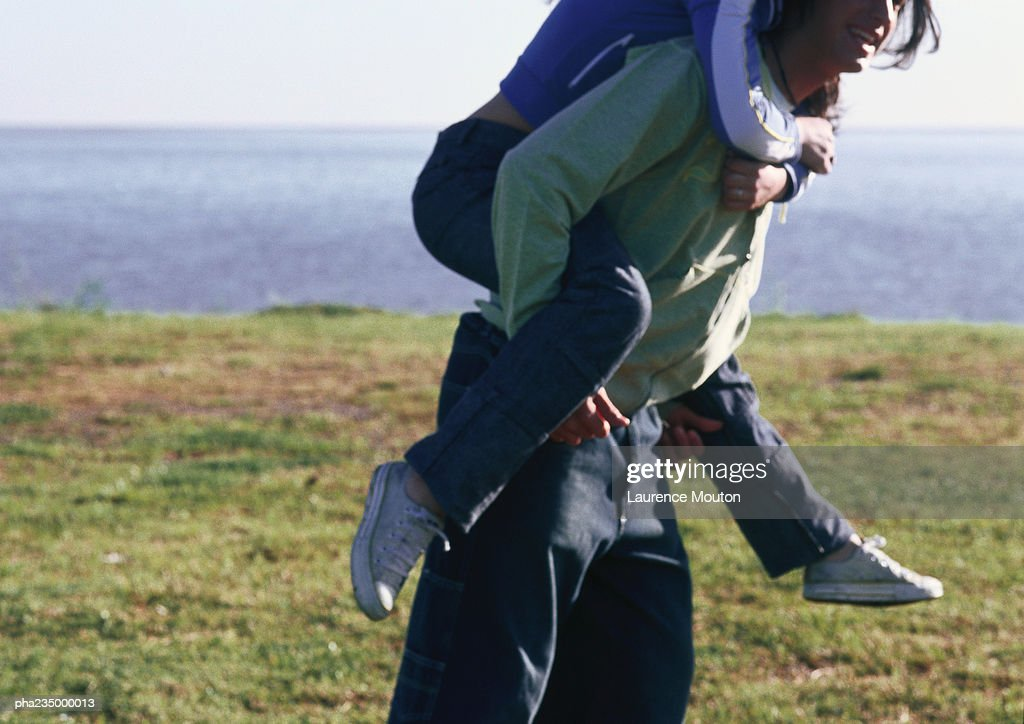 Man carrying woman on his back by the water. : Stockfoto