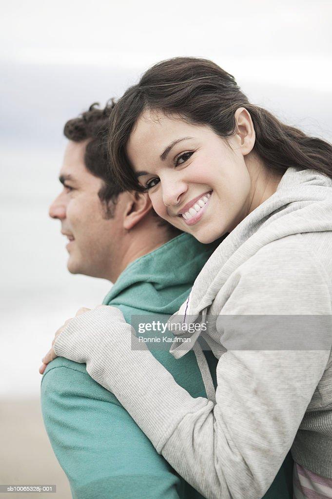 Man carrying woman piggyback at beach, close-up, smiling : Foto stock