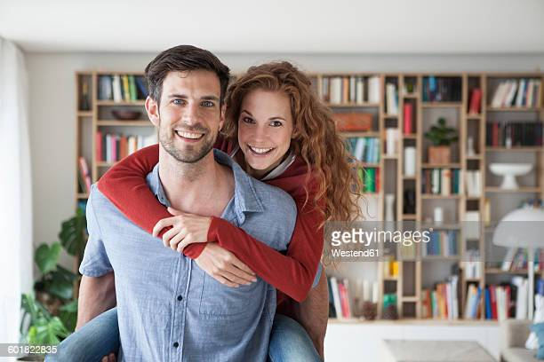Man carrying woman piggyback at home