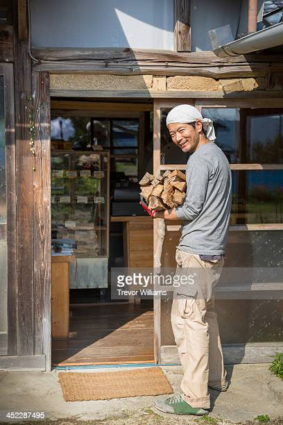 man carrying wood to supply stone oven bakery