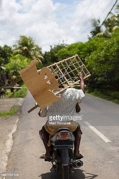 Man carrying wooden furniture on scooter