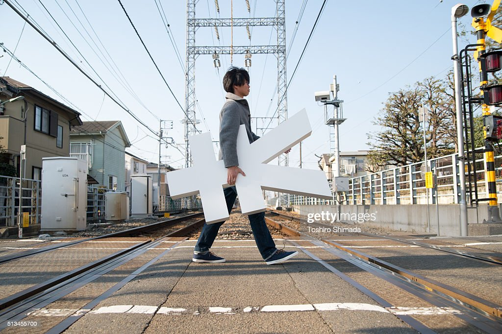 A man carrying Yen shape object and crossing : ストックフォト