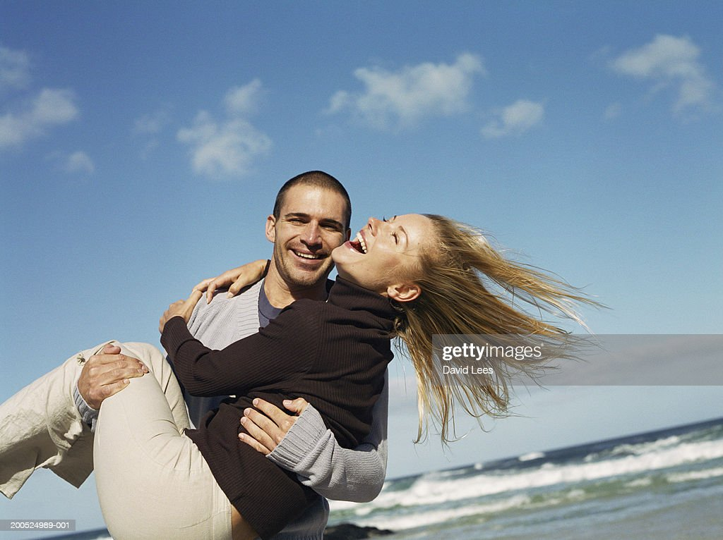 Man carrying young woman on beach, smiling : Stock Photo