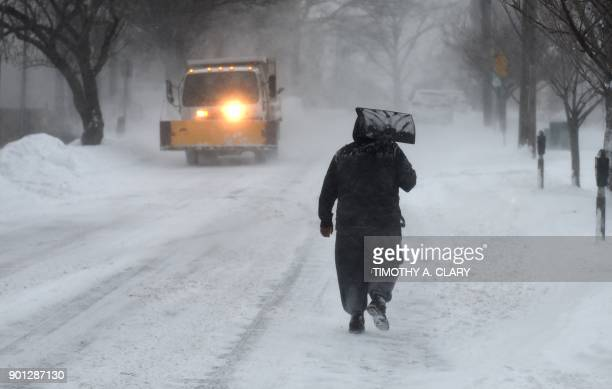 A man carrys a shovel up the middle of the street in Greenwich Connecticut on January 4 2018 A giant winter 'bomb cyclone' walloped the US East Coast...
