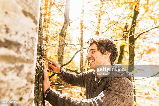 man carving into tree trunk with penknife - tree trunk stock pictures, royalty-free photos & images