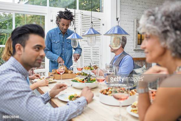 Man carving meat while friends talking during meal