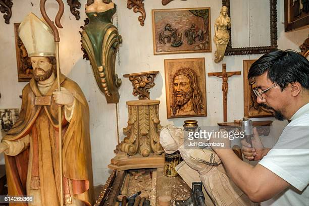 Man carving religious icon statue in souvenir gift shop