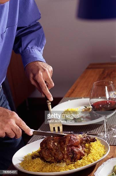 Man carving roast cornish hen