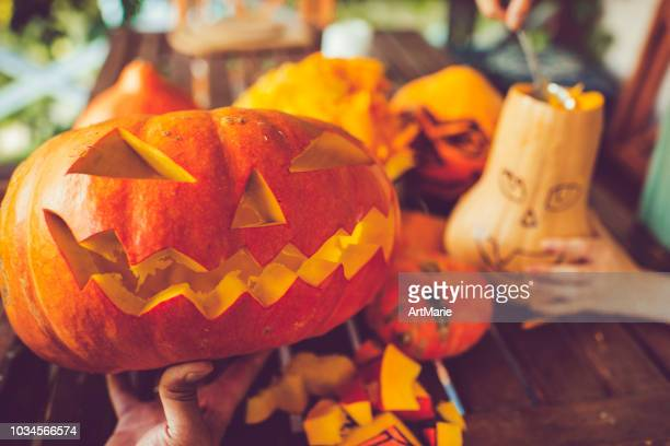 man carving spooky face on a pumpkin in halloween - pumpkin stock pictures, royalty-free photos & images