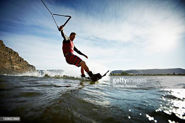 man carving turn on wakeboarding view from water - waterskiing stock photos and pictures