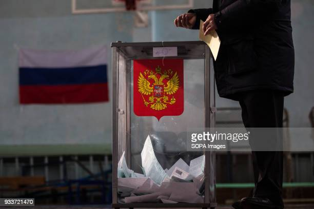 A man casts ballot paper during the 2018 Russian presidential election at a polling station in StPetersburg The Presidential election of Russia is...