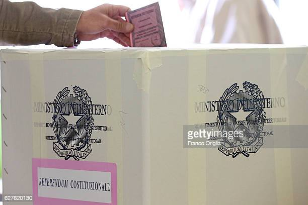 A man casts her ballot for a referendum on constitutional reforms at a polling station on December 4 2016 in Rome Italy The result of the government...