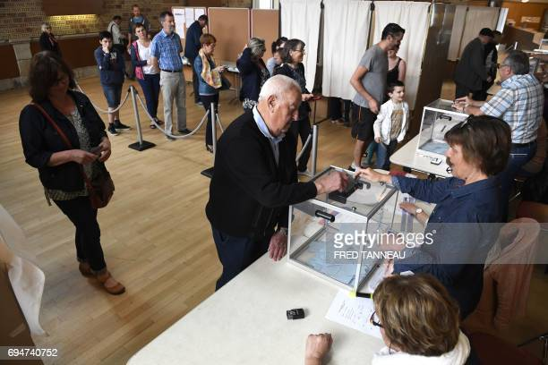 A man casts his ballot as others queue to vote at a polling station in CarhaixPlouguer western France during the first round of the French...