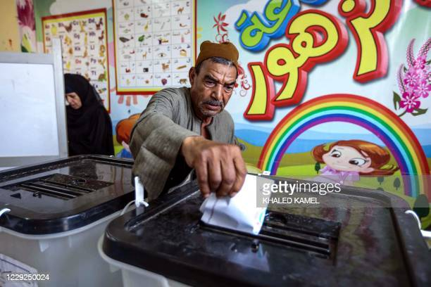 Man casts his ballot at a polling station in El-Ayyat, south of the Egyptian capital on October 24 during the first stage of the lower house...