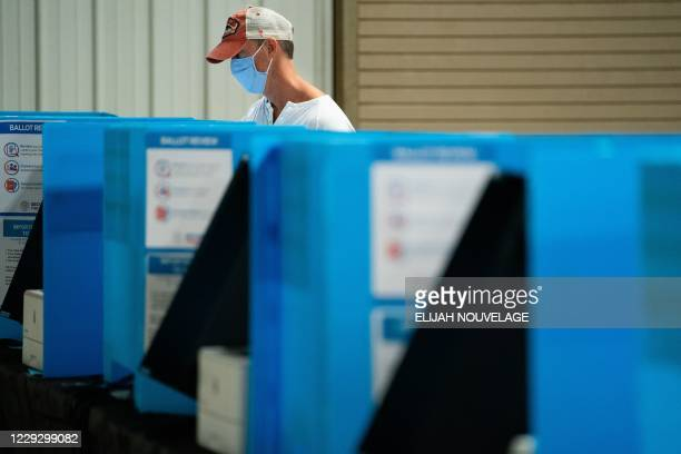 Man casts his ballot at an early voting location at the Gwinnett County Fairgrounds on October 24 in Lawrenceville, Georgia. - Neighbors and...