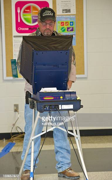 Man casts his ballot at the Battlefield High School November 6, 2012 in Gainesville, Prince William County, Virginia. After a long and bitter White...