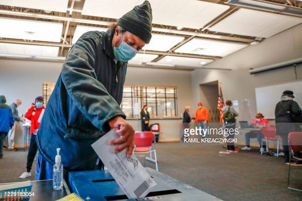 Man casts his ballot at the Washington Park Library on the first day of in-person early voting for the November 3, 2020 elections in Milwaukee,...