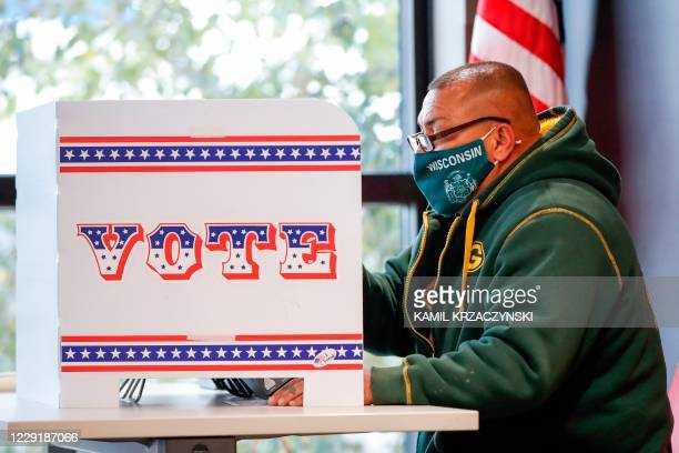 Man casts his ballot at Tippecanoe Library on the first day of in-person early voting for the November 3, 2020 elections in Milwaukee, Wisconsin, on...