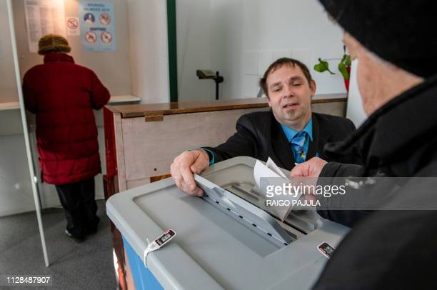 Man casts his ballot in a polling station during Estonia's general election in Tallin, on March 3, 2019. - Estonias centre-left coalition is fighting...