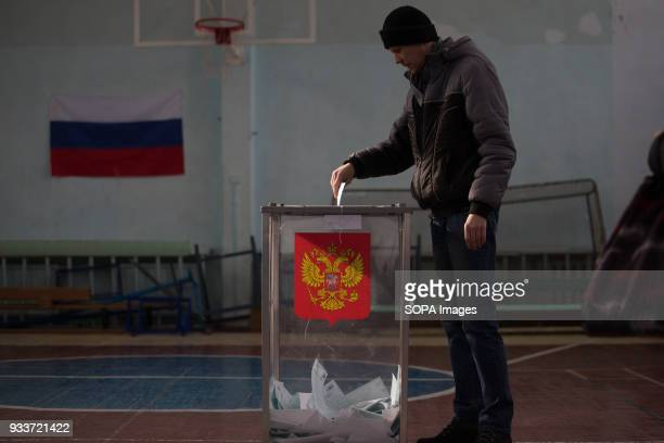 A man casts his ballot paper during the 2018 Russian presidential election at a polling station in StPetersburg The Presidential election of Russia...
