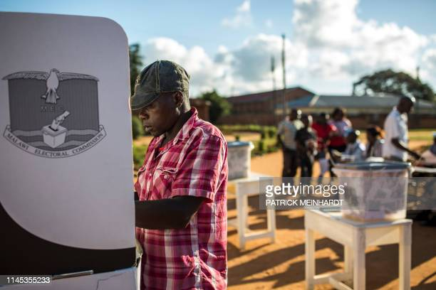 A man casts his vote at CCAP Primary School polling station during the Malawi Tripartite general elections in Mzuzu on May 21 2019 Malawi went to the...